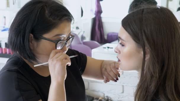 Female visagist paints lips of model in beauty salon.
