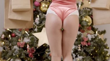 Sexual model is posing for Christmas photo shoot in modern studio.