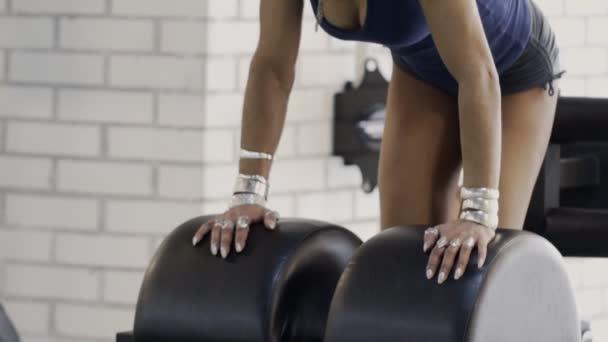 Africká americká atletka zastává pozici těla na cvičný stroj.