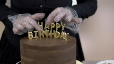 Rukou ženské confecrioner, který je dokončení dát dopis svíčky na vrchol čokoládového dortu, zblízka