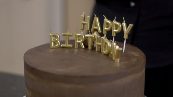 Confectioner shows gold letters on a chocolate cake for the holiday.