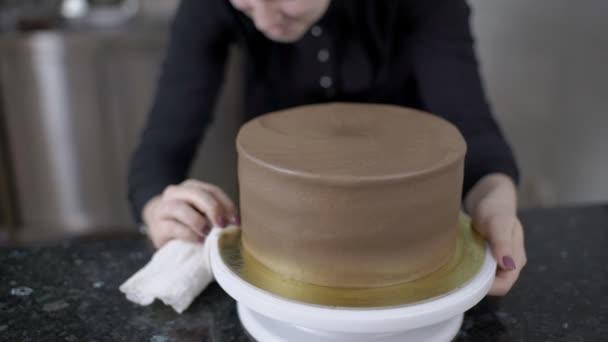 Ženské cukrář je čištění desky s čokoládový dort na oslavu narozenin