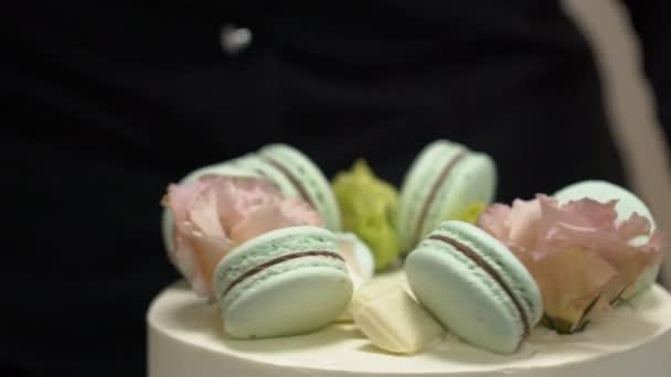 Cukrář zdobí dort s čokoládou, makronky a květiny