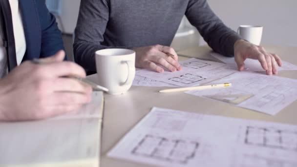 Dva mužské architekti jednají stavební plány, zblízka.