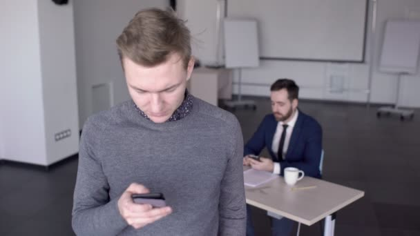 Young man is using smartphone, standing in modern office indoors.