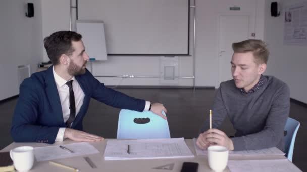 Mladí zaměstnanci pracují v moderních kancelářských budovách u stolu