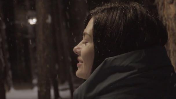 Mladá žena stojí ve sněhem pokryté lese v pozdě večer