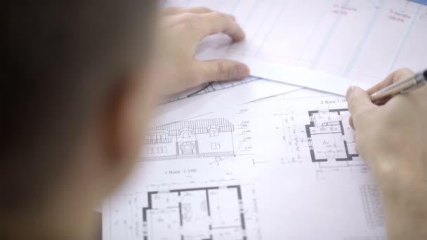 Porträt eines männlichen Architekten, der den Bauplan des Hauses korrigiert.