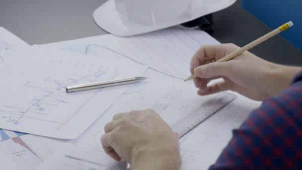 Mužské profesionální práce s technickou dokumentací v moderní kanceláři