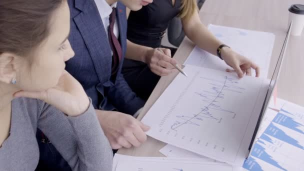 Mladí odborníci diskutují blueprint sedí u stolu v přední společnosti