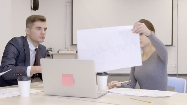 I commercianti giovani lavorano sul modello che si siede al tavolo in ufficio moderno
