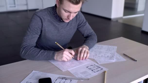 Portrait du jeune architecte qui travaille sur le plan du