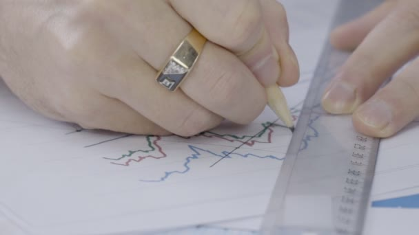 Close-up of a man drawing a line on a ruler on the chart.