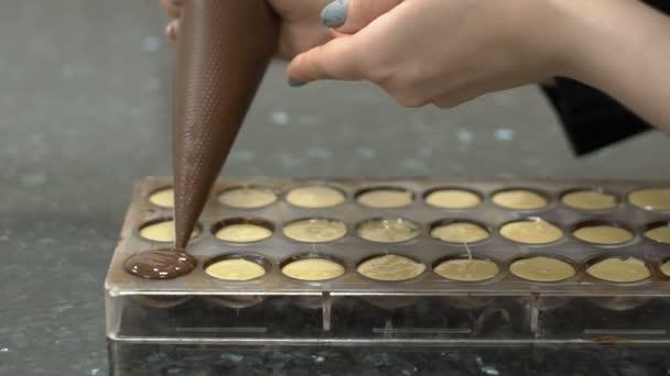 Žena se vztahuje na cukroví s tekuté čokolády z cukrářského sáčku.