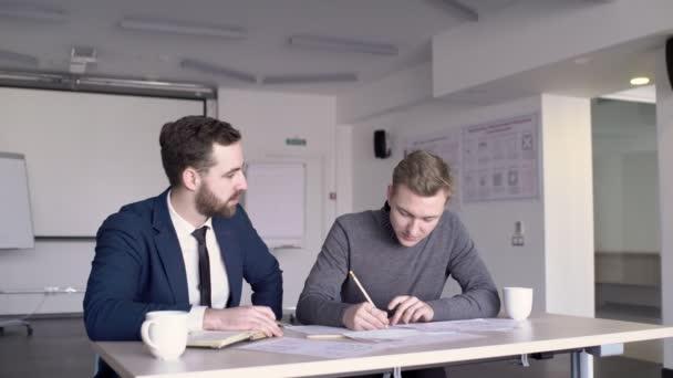 Mladý muž student a profesor architektury pracují společně