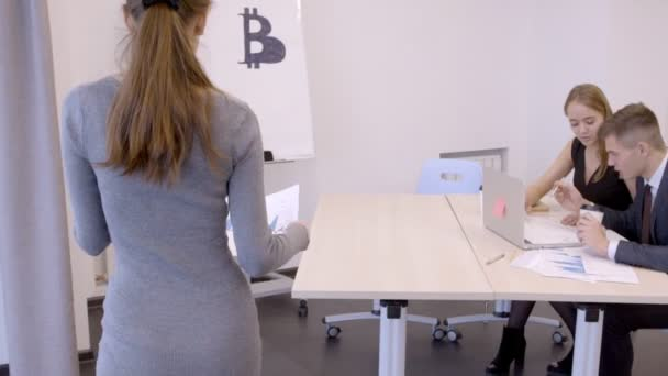 Team of young analysts works at the office of management of bitcoins.
