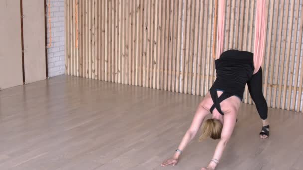 Middle aged woman doing gymnastic exercise in hammock in modern studio.