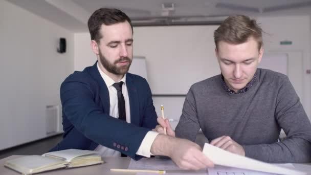 Professionisti di uomini stanno lavorando sulla cianografia al tavolo in ufficio moderno