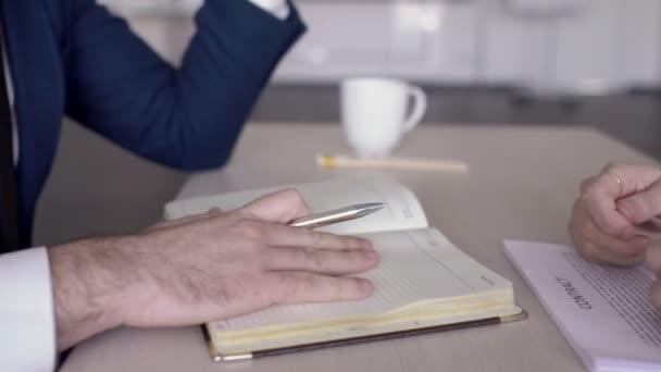 Sur table homme avec un stylo met sa signature sur le contrat de