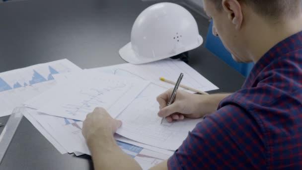 Na stole je inženýr pracující na projektu výstavby na dokumentech.