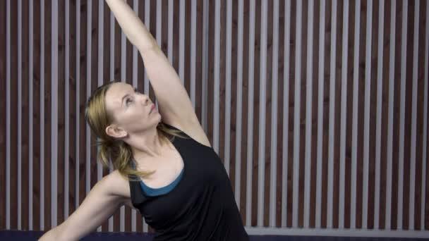Žena v černém tričku táhne ruku během gymnastika tříd