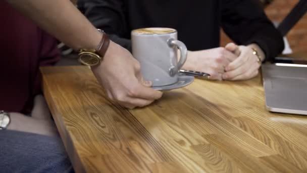Detail pro dva lidi číšník na stole přináší horké kávy a čaje