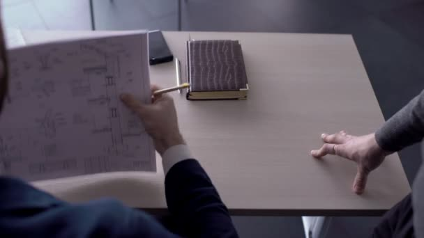Na stole muž schvaluje stavební projekt a podepíše smlouvu