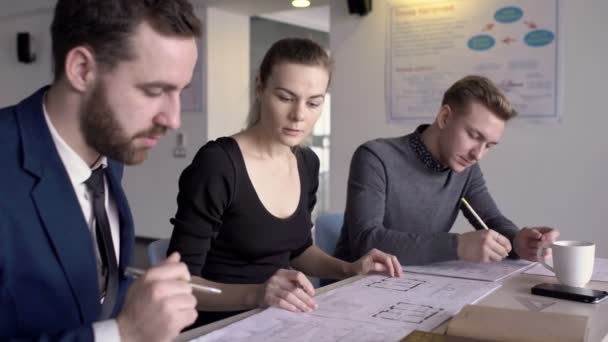 Three architects are discussing building blueprints in their office.