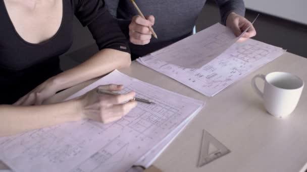 Mladí zaměstnanci pracují na plánu u stolu v moderní kanceláři.