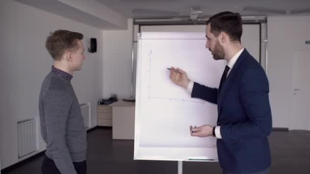 Podnikatel je kreslení grafu na tabuli v moderní kanceláři