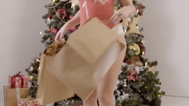 Erotik-Model mit nackten Beinen bewegt sich mit Geschenken, Weihnachtsbaum im Innenbereich