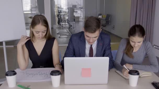 Mladí hosté týmová práce u stolu pomocí přenosného počítače v ucastnin
