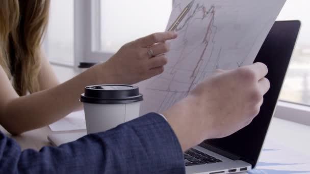 Na stůl ženu s perem v ruce ukazuje ten graf na papíře.