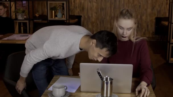 For laptop sits couple and man is surprised looking at monitor of woman.