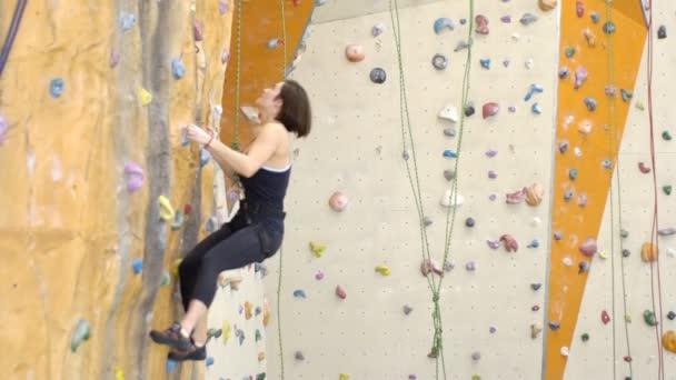 A hegymászó nő akasztott falon tornateremben edzés közben.