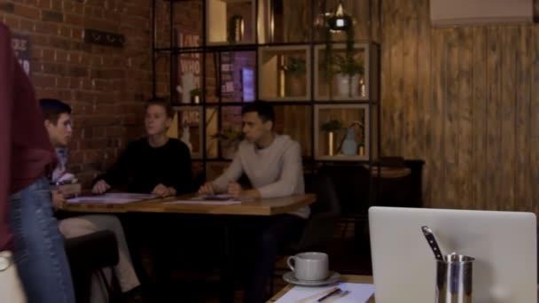 Junge Männer diskutieren Gründungsprojekt am Tisch im Café.