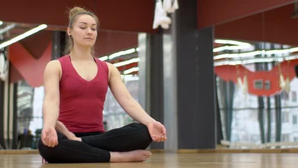 Mladá dáma má meditaion v moderní tělocvična se zrcadly na zdech.