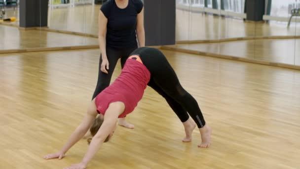 Jóga oktató tanítja a fiatal nő pózol egy kutya az edzőteremben