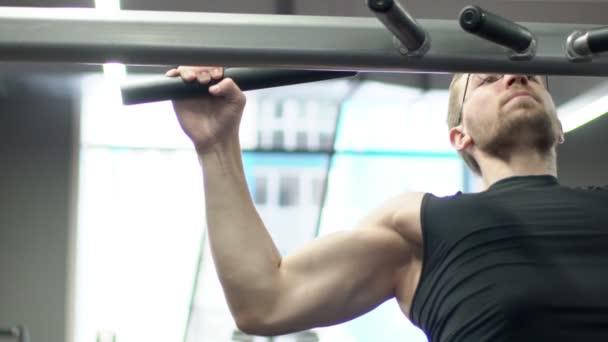 Portrét sportovce, který se s námahou v široké přilnavost lat pulldown v moderní tělocvičně