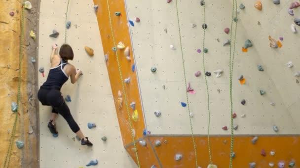Karcsú nő fokozatban felemelkedik a mászófal, a tornateremben.