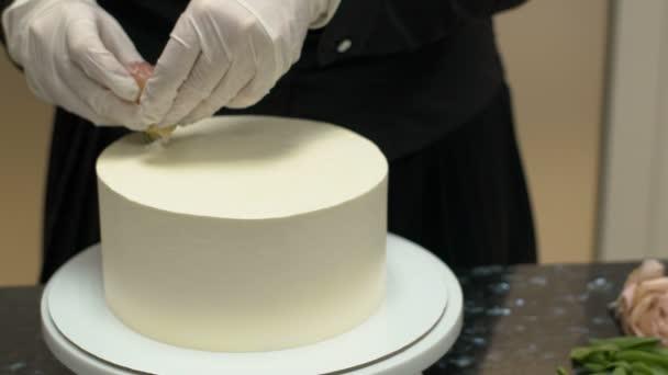 Mladí kuchaři zdobí dort s květinou na kuchyňském stole v restauraci