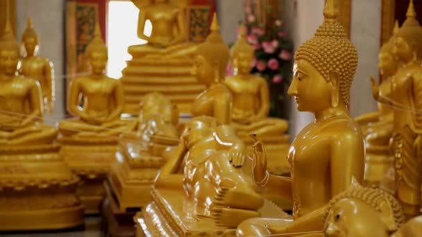 Buddha statues stand in Buddhist temple in background of window and flowers, golden figures are in lotus position, they symbolize faith, peace, wisdom.