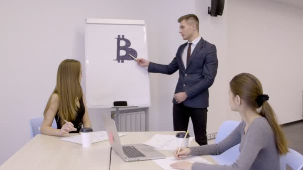 Young businessman presenting his bitcoin investment plan to his female colleagues in the office, slow motion.
