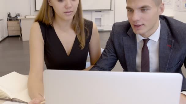 Businessman and businesswoman working on computer together in the office, slow motion.