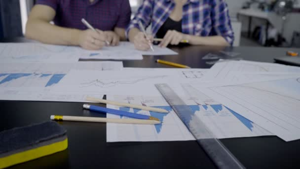 Mladí specialisté napsat na papír v moderních kancelářských budovách