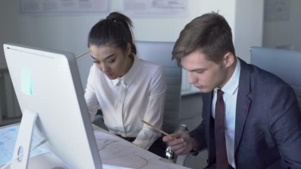 V kanceláři jsou muž a žena sedí u počítače a diskusi o projektu. 4k