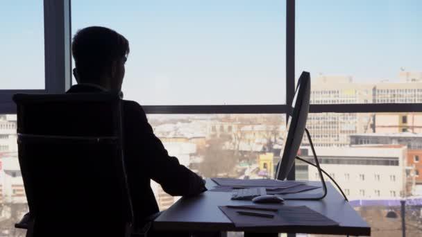 Silueta portrét podnikatele ukončení telefonního hovoru a pokračovat v práci na počítači ve své pracovně s výhledem na město. 4k