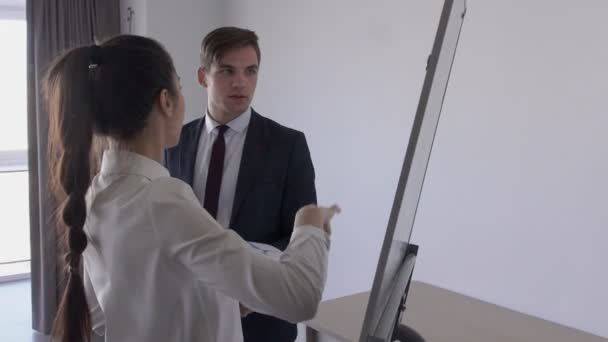Two young professionals are discussing ideas, standing near magnetic board in office interior, man and woman talking about new project, pointing at charts, holding documents.