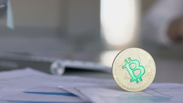 Close up of golden bitcoin coin standing on papers with reports in the office with hands of businesswoman on background.