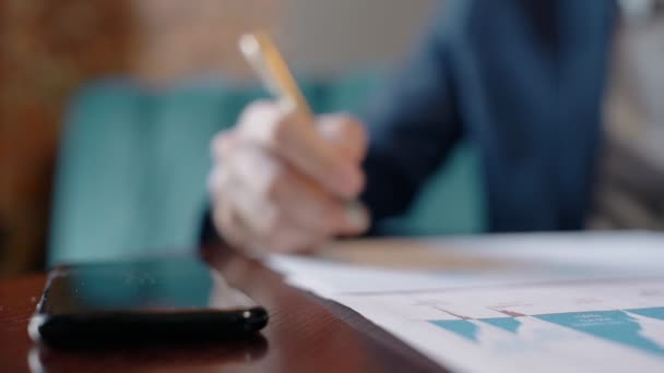 Közelkép üzletember kézzel írás a papír jelentést, és figyelembe smartphone a táblából, kávézó.